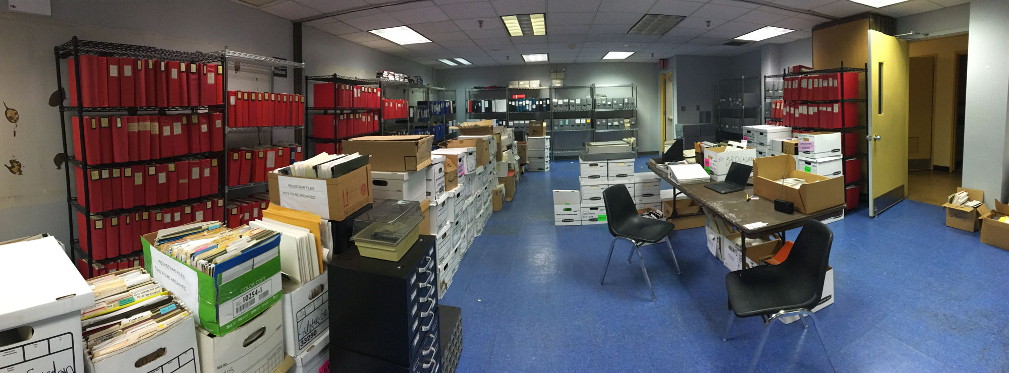 A panaromic view of a large office space with shelves of red folders lining the walls and file boxes in down the middle.