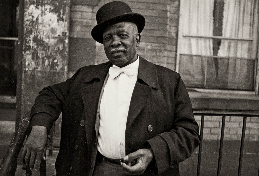Older black gentleman wearing a suit with bowtie and bowler hat, standing with arm leaning on a bannister in front of a brick building