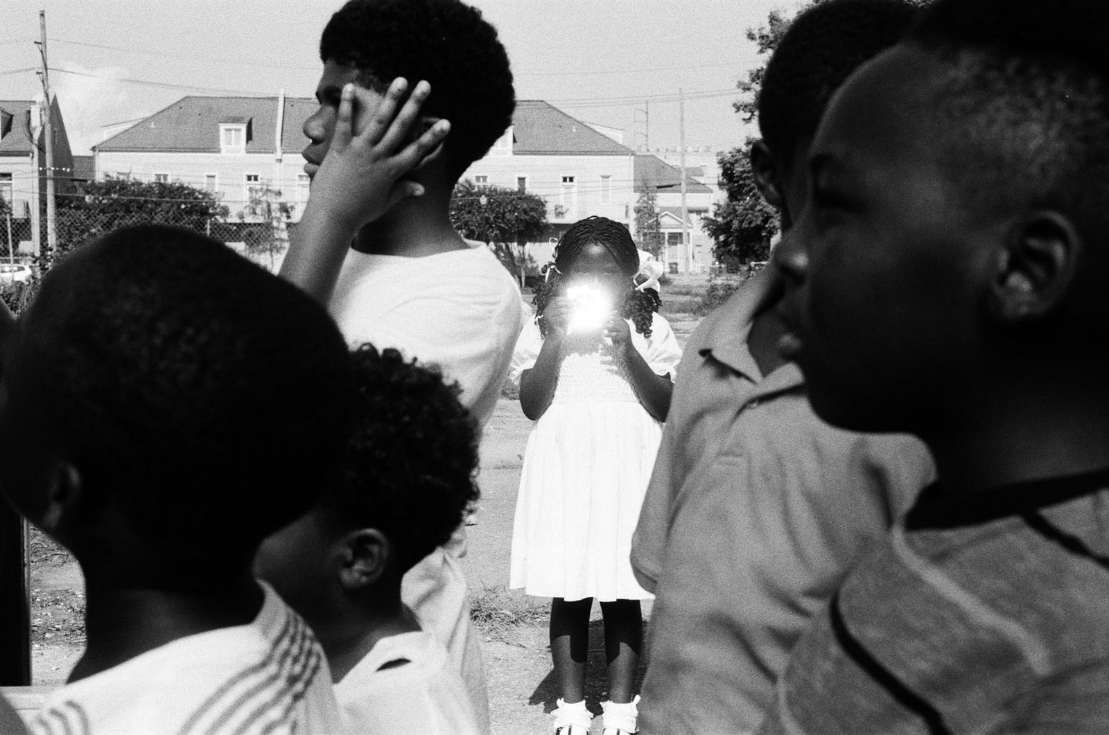 A black-and-white image of a young Black girl in a white dress holding a reflective object that hides her face.