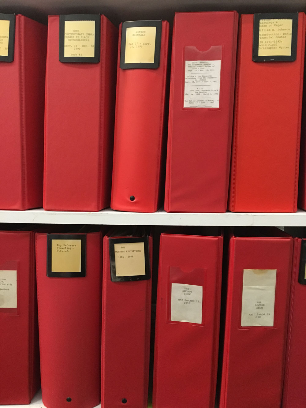 Two shelves displaying large red labeled binders.